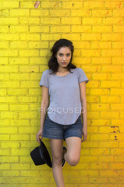 Young woman leaning against yellow brick wall — Stock Photo
