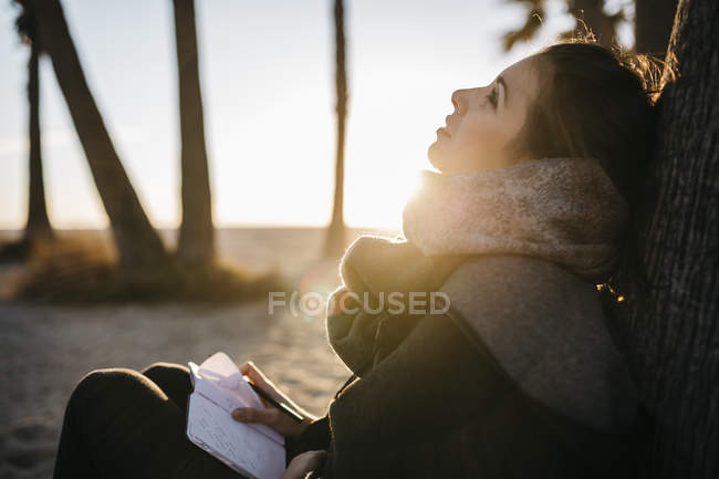 Woman with notebook sitting on beach in winter — Stock Photo