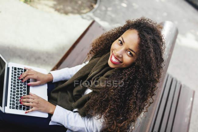Улыбающаяся молодая женщина с ноутбука на скамейке — стоковое фото