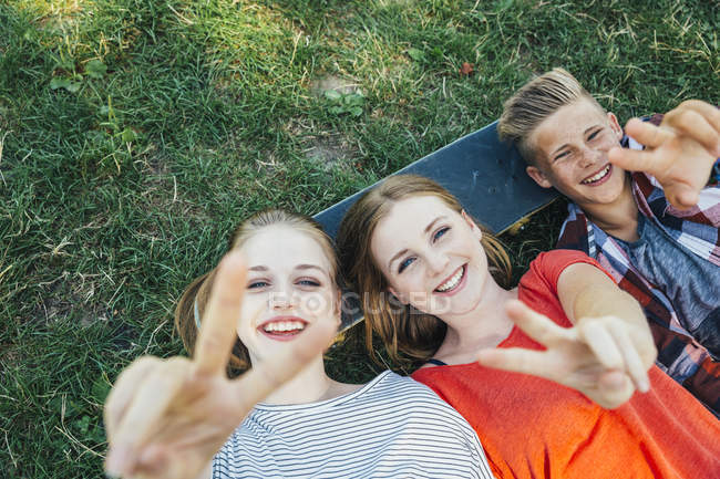 Three happy teenage friends lying on skateboard in meadow making victory sign — Stock Photo
