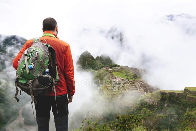 Perú, región de Machu Picchu, hombre mirando la ciudadela de Machu Picchu y la montaña Huayna - foto de stock