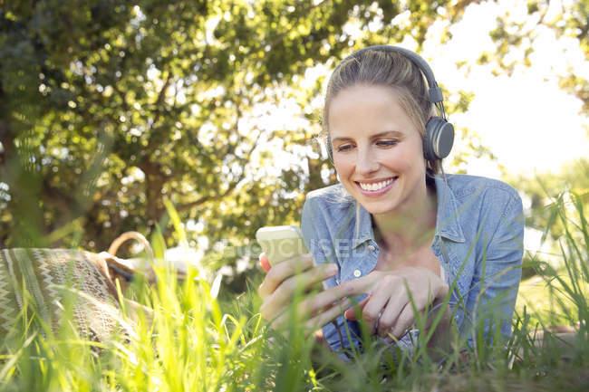Улыбающаяся женщина лежит на лугу и слушает музыку со смартфона — стоковое фото