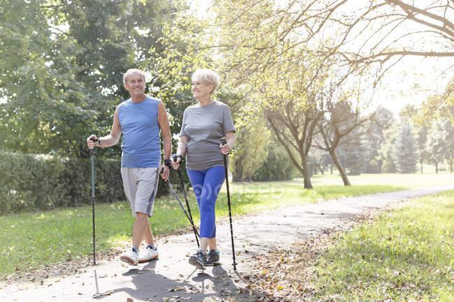 Старший пара робити нордичної ходьби разом у парку — стокове фото