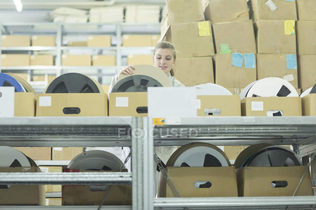 Jeune femme dans l'entrepôt en tenant la bobine de boîte en carton — Photo de stock