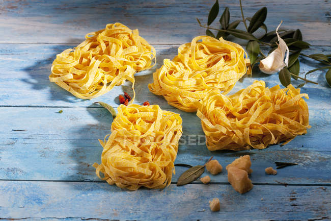 Raw Tagliatelle, chili pods, sage leaves, parmesan and garlic clove — Stock Photo