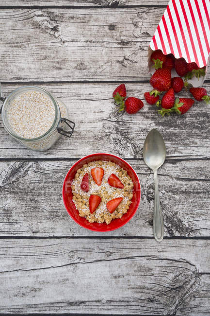 Granola con amaranto palomita y fresas en un tazón de madera gris con ingredientes - foto de stock