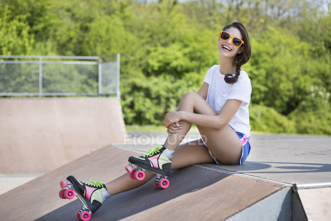 Smiling female inline-skater with sunglasses sitting on ramp in skatepark — Stock Photo