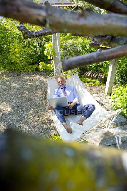 Uomo d'affari sdraiato in amaca in un giardino utilizzando il computer portatile — Foto stock