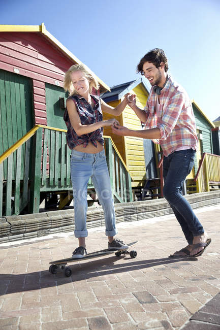 Young man helping girlfriend on skateboard at colorful beach huts — Stock Photo