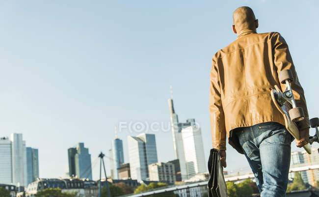 Man on the go carrying skateboard and briefcase — Stock Photo