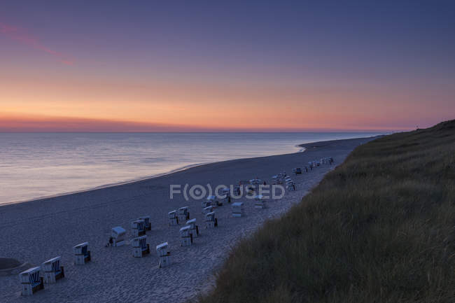 Germany, North Frisia, Sylt, Rantum, beach with hooded beach chairs at sunset — Stock Photo