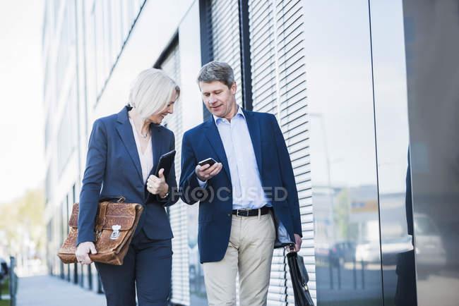 Imprenditori che camminano in strada controllando smartphone — Foto stock