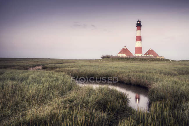 Lighthouse by the grassy field and brook — Stock Photo