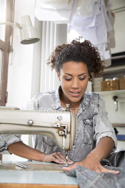 Молодий швачка з швейні машини, що працюють в майстерні — стокове фото