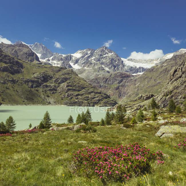Italia, Lombardia, lago vicino a Chiesa in Valmalenco, Sasso Rosso con il ghiacciaio — Foto stock