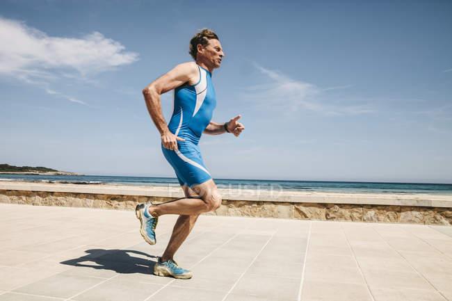 Зрілі кавказька чоловічий triathlet вздовж набережній біля пляжу — стокове фото