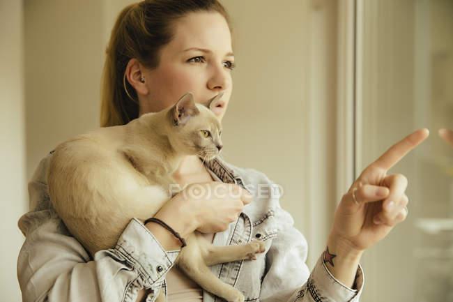 Donna con gatto birmano alla finestra — Foto stock