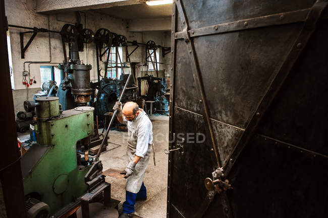 Senior Schmied arbeitet in Hammermühle — Stockfoto