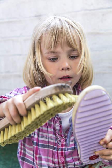 Маленькая девочка чистка обуви — стоковое фото