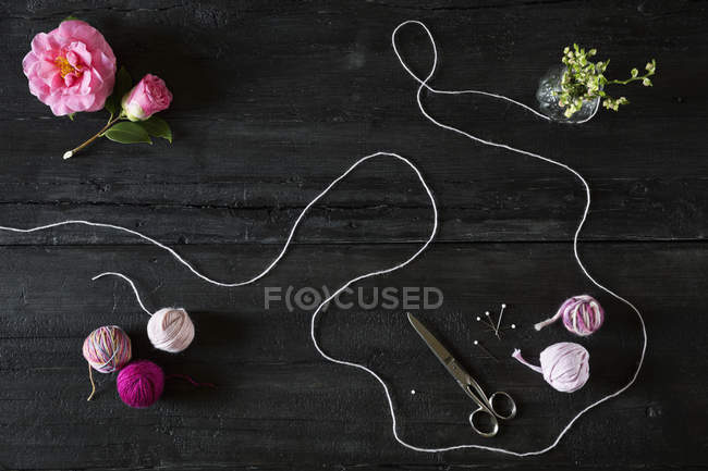 Arrangement of balls of wool, scissors, fixing pins and blossoms — Stock Photo