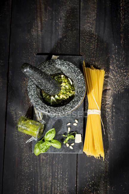 Preparing pesto alla genovese with mortar, uncooked spaghetti — Stock Photo