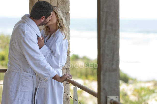 Young couple wearing bathrobes kissing in beach house — Stock Photo