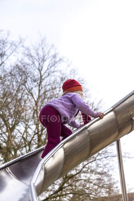 Little girl playing on slide — Stock Photo