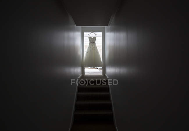 Wedding dress hanging in door case — Stock Photo
