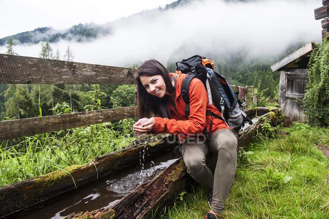 Австрії, Altenmarkt-Zauchensee, молода жінка мандрівного відпочиваючих при фонтан — стокове фото