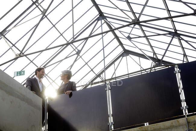 Два общения деловых людей, стоя в современном здании — стоковое фото