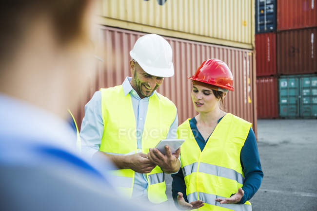 Woman and smiling man with safety helmets and digital tablet at container port — Stock Photo