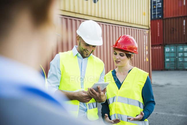 Femme et homme souriant avec des casques de sécurité et tablette numérique au port de conteneur — Photo de stock