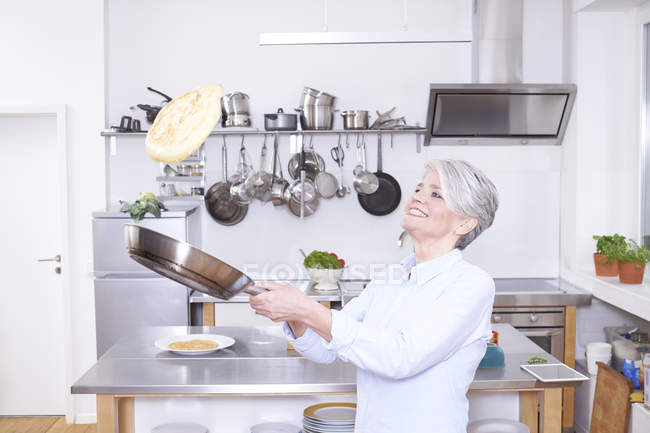 Mujer madura en la cocina vomitando panqueque en la sartén - foto de stock