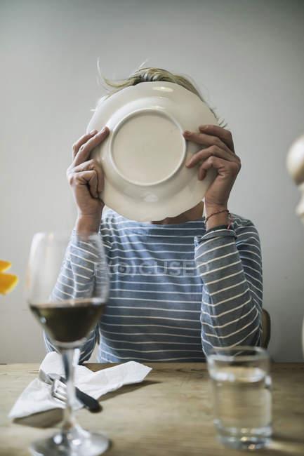Mujer lamiendo un plato en casa - foto de stock