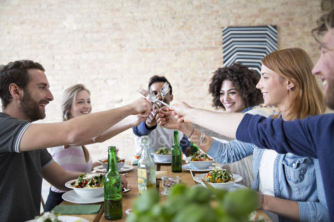 Happy friends eating together at table — Stock Photo