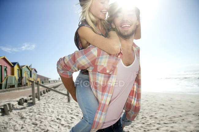 Young man carrying girlfriend piggyback on beach — Stock Photo