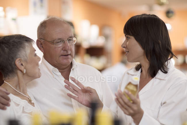 Female health shop pharmacist advising senior couple — Stock Photo