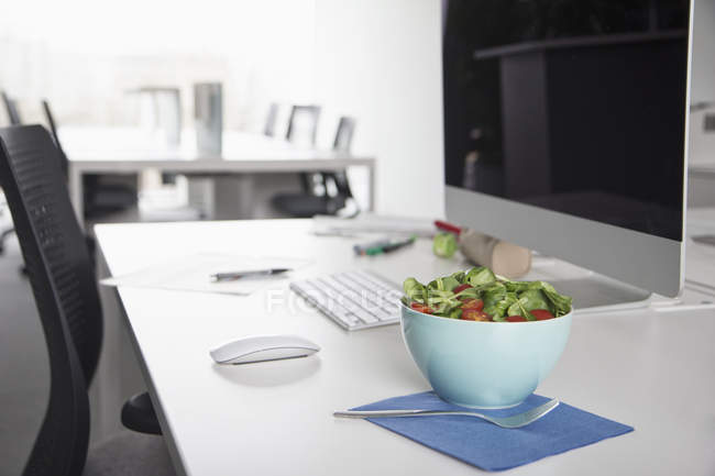 Bowl with garnished salad on a desk in an office — Stock Photo