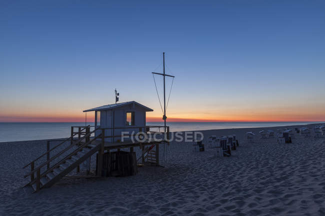 Germany, North Frisia, Sylt, Rantum, view to the beach with hooded beach chairs and attedant at sunset — Stock Photo