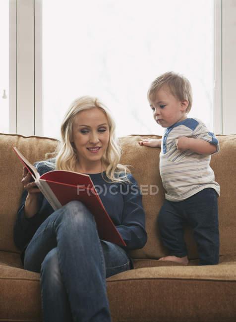 Мама показывает малышу книгу с картинками на диване — стоковое фото
