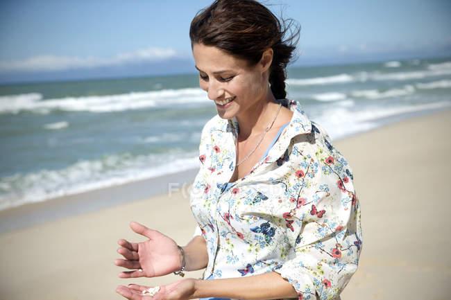 Retrato de mulher sorrindo olhando para conchas em sua mão — Fotografia de Stock