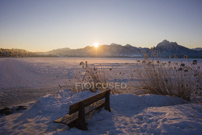 Germany, Allgaeu, East Allgaeu, near Fuessen, Lake Hopfensee in winter against the morning sun — Stock Photo