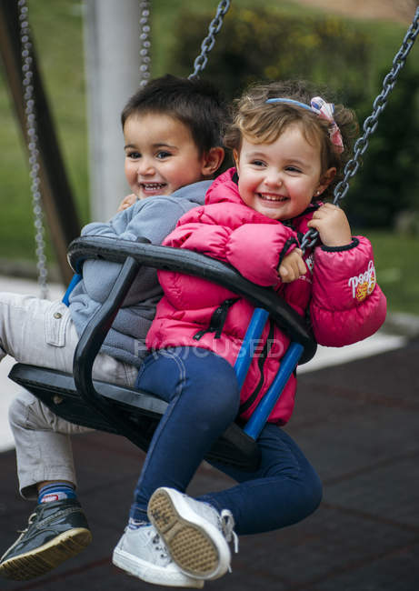 Toddler girl and boy sitting and laughing on swing — Stock Photo