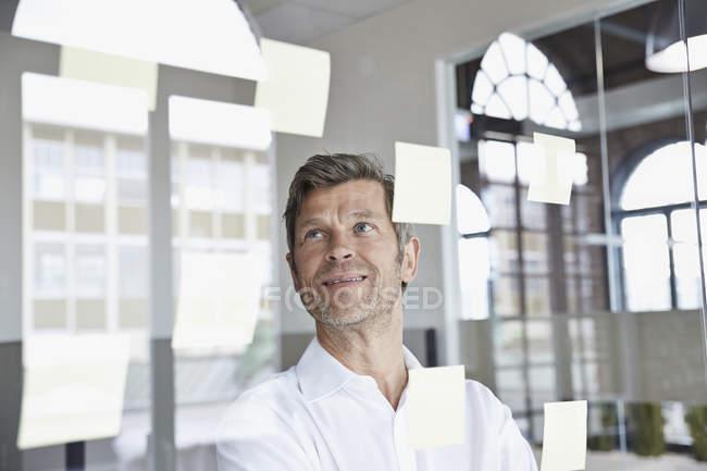 Homme d'affaires avec des notes autocollantes sur la vitre au bureau — Photo de stock