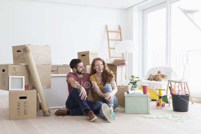 Pareja joven en piso nuevo con cajas de cartón, sentada en el suelo - foto de stock
