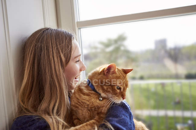 Female teenager with cat looking through window — Stock Photo