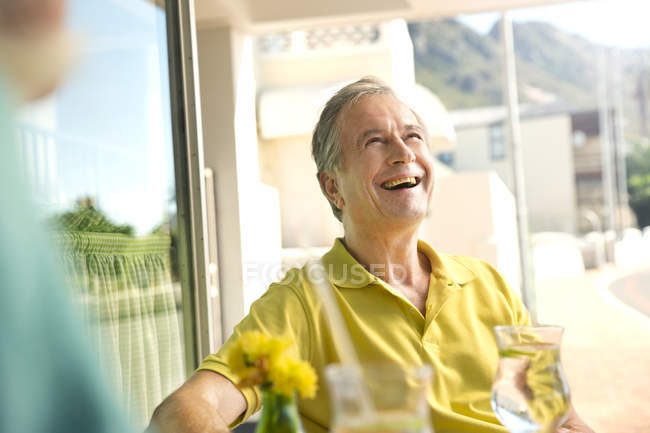 Portrait of laughing senior man sitting in a cafe — Stock Photo