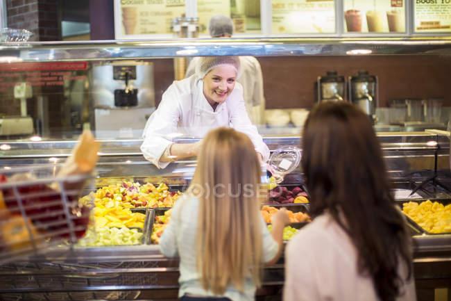 Mãe e filha comprando salada de frutas no supermercado — Fotografia de Stock