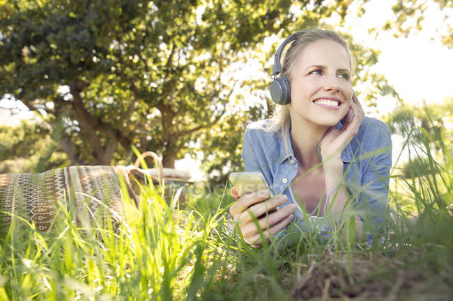 Smiling woman lying on meadow listening to music from smartphone — Stock Photo