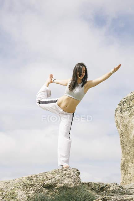 Женщина, занимающаяся йогой на горе — стоковое фото